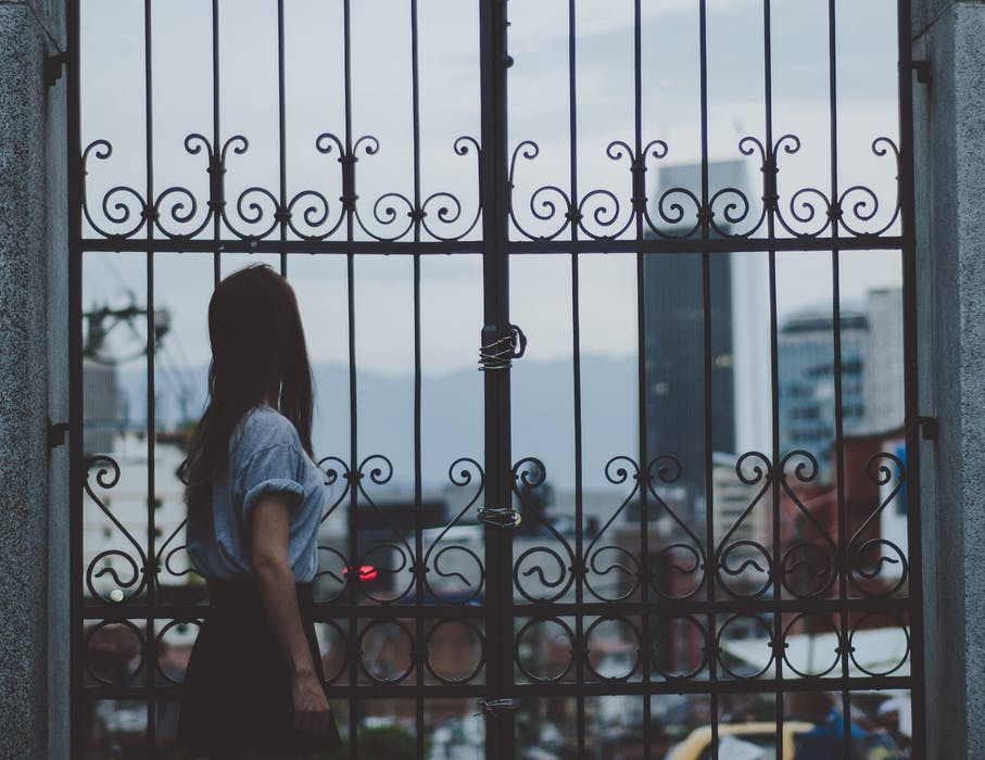 woman standing behind wrought iron fences